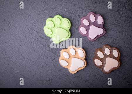 Cute colored paw shape soap on dark dark background - Stock Photo