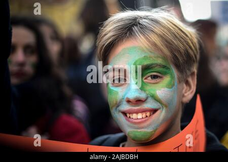 Turin, Italy - 29 November, 2019: Protester with painted face smiles during 'Fridays for future' demonstration, a worldwide climate strike against governmental inaction towards climate breakdown and environmental pollution. Credit: Nicolò Campo/Alamy Live News - Stock Photo