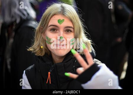 Turin, Italy - 29 November, 2019: Protester with face painted in green gestures during 'Fridays for future' demonstration, a worldwide climate strike against governmental inaction towards climate breakdown and environmental pollution. Credit: Nicolò Campo/Alamy Live News - Stock Photo