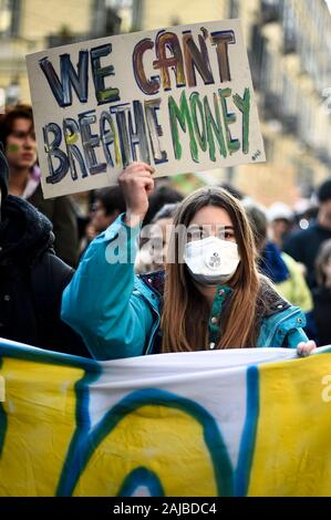 Turin, Italy - 29 November, 2019: Protester holds placard reading 'We can't breathe money' during 'Fridays for future' demonstration, a worldwide climate strike against governmental inaction towards climate breakdown and environmental pollution. Credit: Nicolò Campo/Alamy Live News - Stock Photo