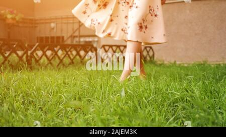 bare feet of slim lady in long pink summer dress walk along lush green grass lawn on warm day close low angle shot copyspace - Stock Photo