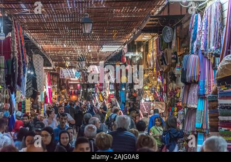 Marrakech, Morocco: People and tourists strolling, booths and stalls in alley nearby Jemma Dar Fna, souk market in Marrakesh medina, crowded bazaar