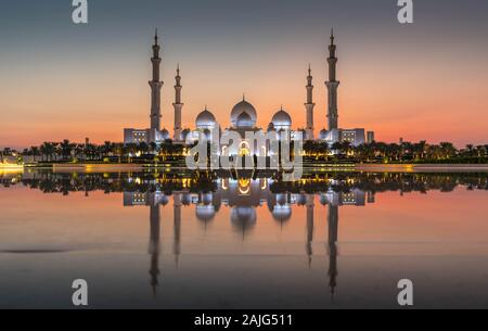 Abu Dhabi, UAE, United Arab Emirates: Abu Dhabi Sheikh Zayed Mosque (also known as Grand Mosque) at dusk, reflection in water, at sunset
