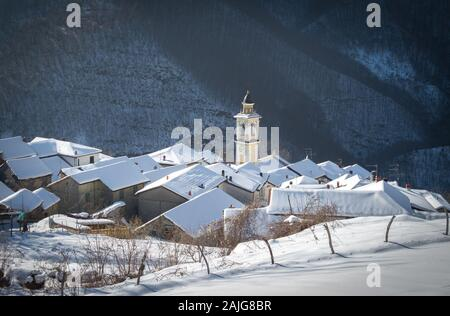 Bertone (Ottone), Piacenza, Italy: Scenic winter view of snow covered picturesque quaint Italian village, church bell tower and fresh snow on rooftops - Stock Photo