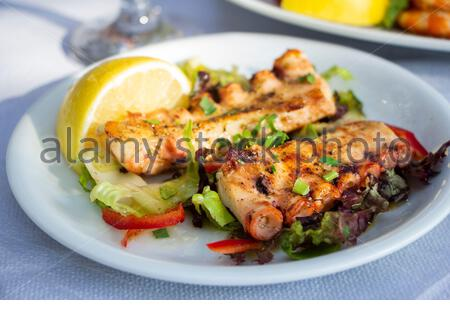 Fried octopus on plate with slice of lemon in taverna in Greece - Stock Photo