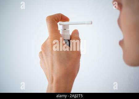 close up view of a female face and hand with spray medicine for a sore throat and cough on a white background - Stock Photo