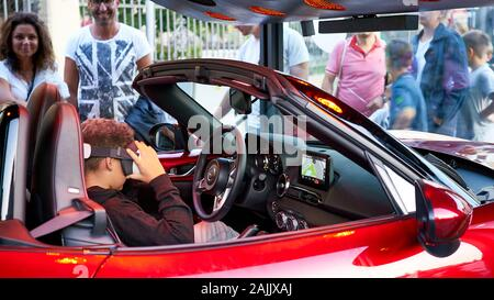 Young boy sits in red sports car and tries driving at high speed using virtual reality glasses while amused parents look on. - Stock Photo