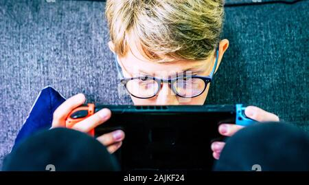 Young and concentrated caucasian child gamer with portable device playing with technology games internet connected with friends - video game addiction - Stock Photo