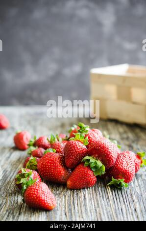 Fresh ripe strawberries on a wooden background. Organic juicy berries. Top view. Copy space for your text.