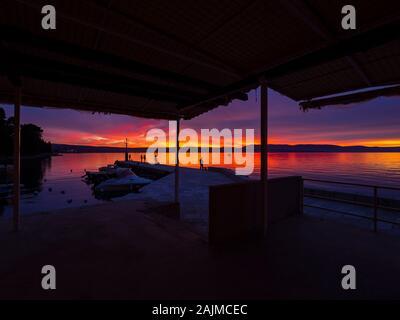 Fishermen before sunset scenery in small harbor in Malinska in Croatia framed by house roof