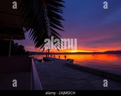 Fishermen view from rear rearview back standing on seawall before sunset scenery in small harbor in Malinska in Croatia natureaddicted natureaddict - Stock Photo