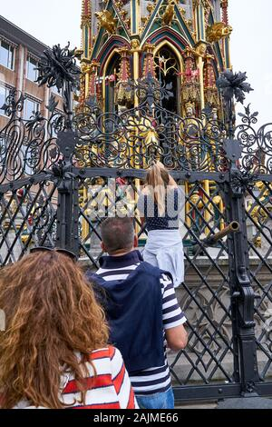 Tourists line up at the 14th century Schoner Brunnen Fountain to bring good luck by turning the brass ring in the market square of Nuremburg, Germany. - Stock Photo