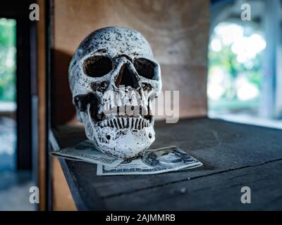 Dirty money skull isolated and dollars paper banknotes bellow - Stock Photo