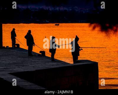 Fishermen silhouette silhouettes silhouetting before sunset in small harbor in Malinska in Croatia - Stock Photo