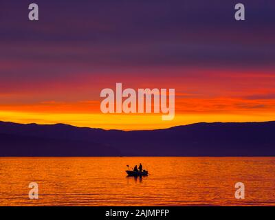 Lonely boat with two fishermen before glorious sunset sea scenery - Stock Photo