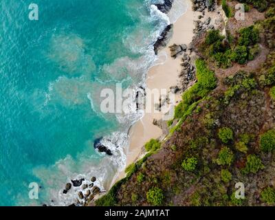 Aerial view of sand beach with rocks and green cliff, top view of a beautiful sandy beach with rocks and waves, blue waves rolling into the shore. Bali, indonesia - Stock Photo