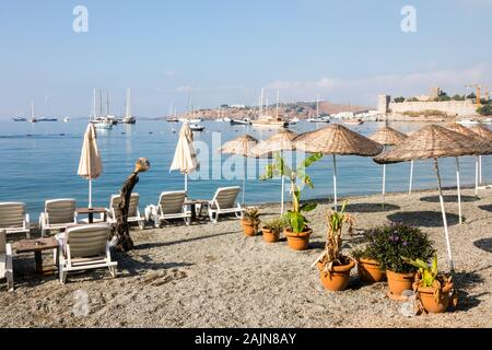 Empty beach in the early morning with boats and castle in the background, Bodrum, Turkey - Stock Photo