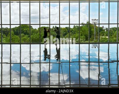 Puerto Princesa City, Palawan, Philippines: Two men standing against windows of a modern building, the sky is reflecting on the floor - Stock Photo