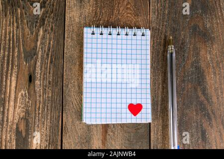 Notepad in cage, with small heart in lower corner and pen, lies on wooden table. The concept of Valentines day holiday or reminder of love to someone. - Stock Photo