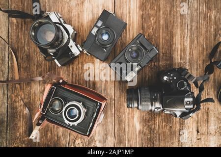 The evolution of the photo cameras on a wooden backraound. Camera technology concept - Stock Photo