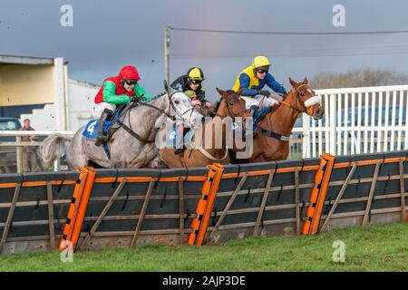Grey horse Arriverderci jumping the last hurdle and running in to win the BoyleSports maiden hurdle race at Wincanton. Ridden by Jonjo O'Neill Jr. Stock Photo