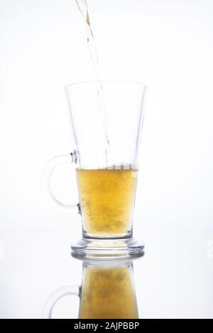 Light unfiltered beer poured into a steaming mug on a white background with reflection - Stock Photo