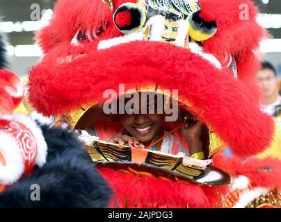 (200105) -- BEIJING, Jan. 5, 2020 (Xinhua) -- Raissa, a girl from Comoros, experiences lion dance at Sias University in Zhengzhou, central China's Henan Province, Oct. 28, 2019. (Xinhua/Li Jianan) - Stock Photo