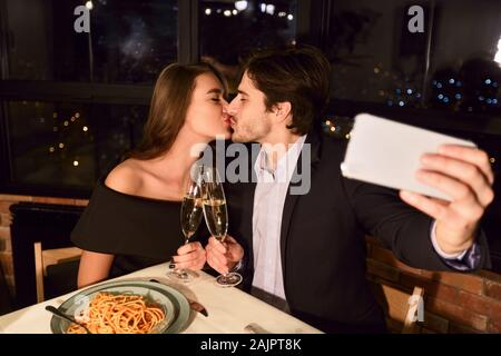 Portrait of kissing couple making selfie photo with smart phone during romantic dinner in restaurant - Stock Photo