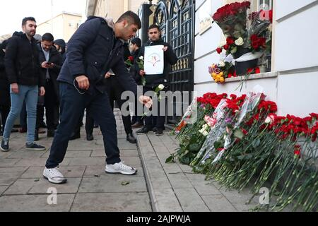 Moscow, Russia. 05th Jan, 2020. MOSCOW, RUSSIA - JANUARY 5, 2020: Iranian students lay flowers outside the embassy of the Islamic Republic of Iran in memory of Islamic Revolutionary Guard Corps Quds Force commander Qasem Soleimani; Soleimani was killed in an airstrike by US drones near Baghdad, Iraq, on 3 January 2020, amid rising tensions between Iran and the United States; Iran's diplomatic missions around the world fly flags at half mast to mourn the death of Soleimani. Anton Novoderezhkin/TASS Credit: ITAR-TASS News Agency/Alamy Live News - Stock Photo