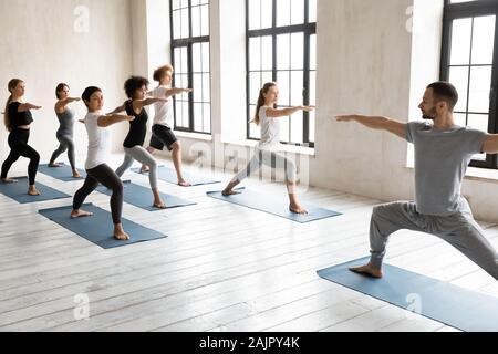 Instructor with diverse people practicing yoga, doing Warrior two exercise - Stock Photo