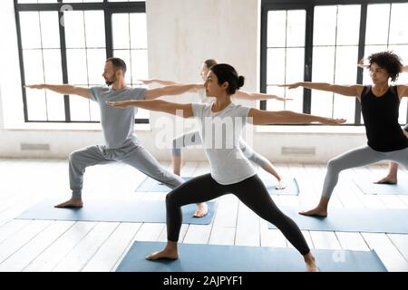 Diverse young people practicing yoga, doing Warrior two exercise - Stock Photo