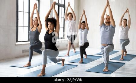 Diverse people doing Warrior one exercise at group yoga lesson - Stock Photo