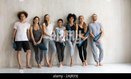 Smiling diverse people with yoga mats standing in yoga studio - Stock Photo