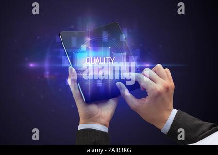 Businessman holding a foldable smartphone with QUALITY inscription, new technology concept