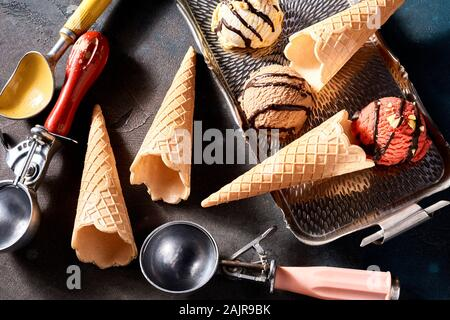 Ice cream still life with wafer cones and scoops viewed from overhead with three flavors of dessert on a small tray for serving