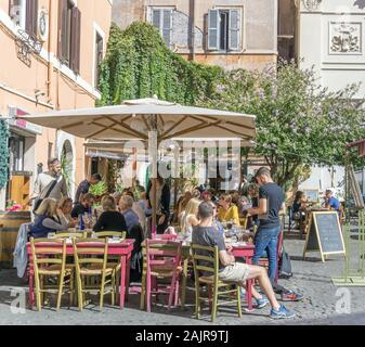 ROME, ITALY - OCTOBER 10, 2017: people are eating outdoors in a typical trattoria in Trastevere, historic district of Rome, Italy