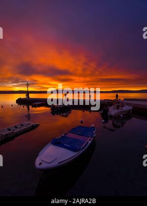 Fishermen before sunset scenery in small harbor in Malinska in Croatia glorious sky peaceful atmospheric seawall Ribarsko selo Haludovo Kvarner - Stock Photo