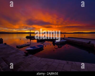 Fishermen before sunset scenery in small harbor in Malinska in Croatia glorious sky peaceful atmospheric seawall Ribarsko selo Haludovo Kvarner