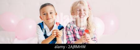 Happy Caucasian funny children eating heart shape red lollipops. Best friends forever. Valentine Day love holiday concept. Web banner header for websi - Stock Photo