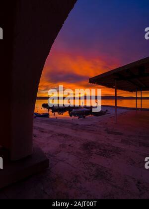 Fishermen standing on edge before sunset scenery in small peaceful harbor in Malinska in Croatia - Stock Photo