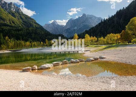 The alpine Lake Jasna with big rocks in the water and surrounded by trees in autumn colors and Alps mountains near Kranjska Gora in Slovenia. - Stock Photo