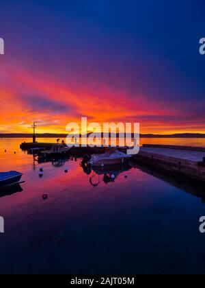 Fishermen before sunset scenery in small peaceful harbor in Malinska in Croatia