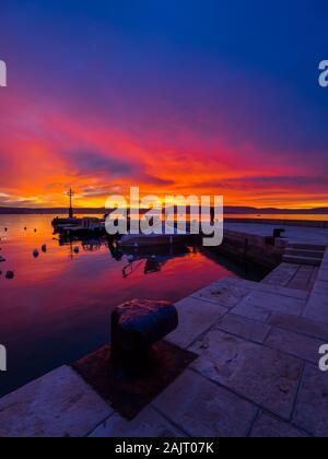 Fishermen before sunset scenery in small peaceful harbor in Malinska in Croatia - Stock Photo