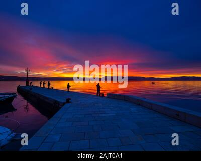 Fishermen before sunset scenery in small peaceful harbor in Malinska in Croatia - Stock Photo
