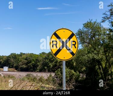Yellow railroad crossing warning sign on rural road with trees and train tracks in background - Stock Photo
