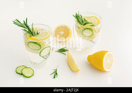 Infused water with rosemary, cucumber and lemon. On white background. Detox and fat burning concept - Stock Photo