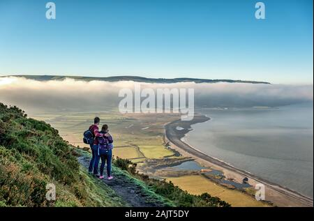 Couple (man and woman) look at an atmospheric inversion layer while walking on a fine winter morning -  Bossington Hill across Porlock Bay, Exmoor, UK