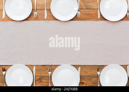 Minimalism. White plate's and gray tablecloth. Festive table set for six people. Wooden background top view mock-up - Stock Photo
