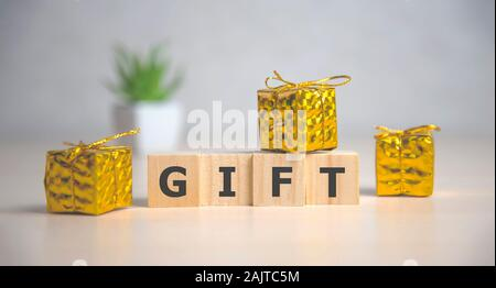 Gift word on wooden cube with background - Stock Photo