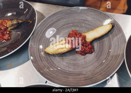 baked eggplants eggplant cooked in the embers on copper plate - Stock Photo